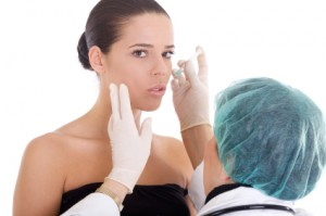 Woman receiving a cosmetic treatment injection to the lips