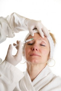 Woman receiving Botox injection to forehead